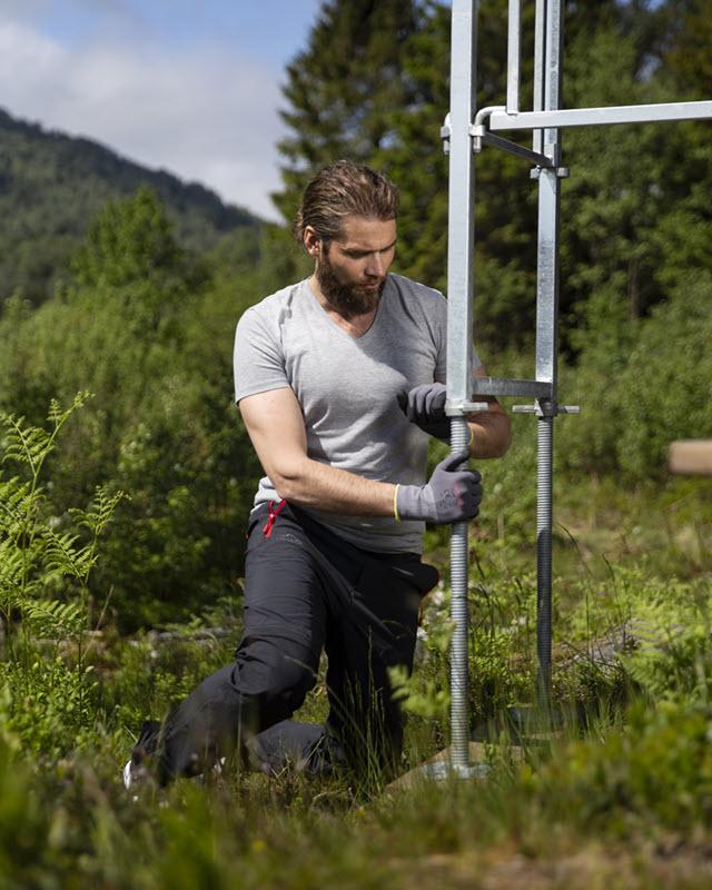 Mann justerer Jamax stillasbein i landlig terreng. Fotografi.