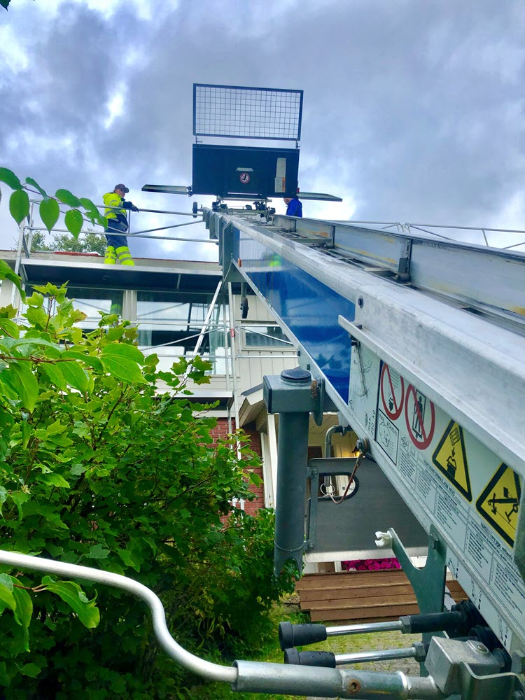 Jamax Böcker Simply Inclined tilhengermontert lift sett i froskeperspektiv mot vegg med arbeider på taket.