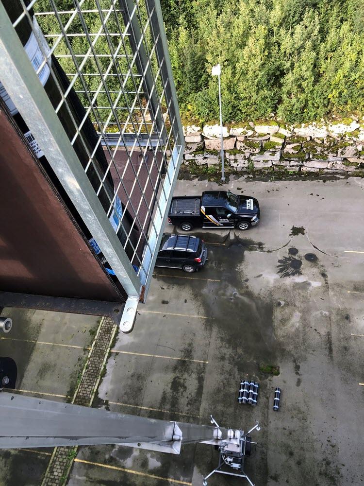 Jamax Böcker Simply Inclined tilhengermontert lift sett i fugleperspektiv mot vegg med arbeider på taket.